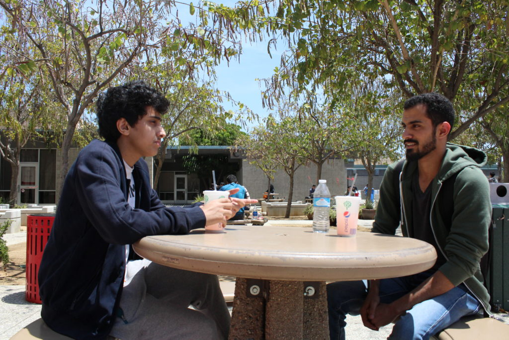 Faisal Aghammas (left), a 20-year-old business major at CSUN and Mashal AlShammari, a 25 year-old medical laboratory sciences major take a break before classes outside of CSUN's International and Exchange Students Center. Photo: Julius Lasin / El Nuevo Sol.